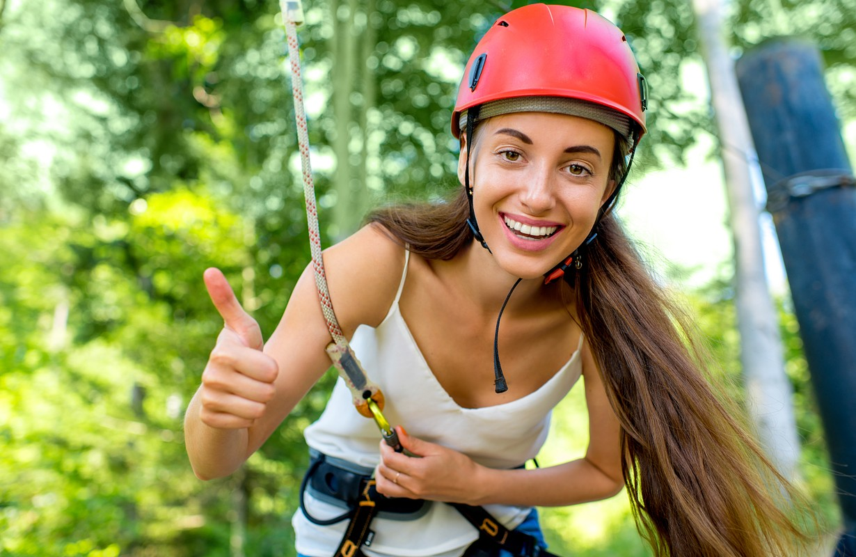Woman in red helmet riding on a zip line