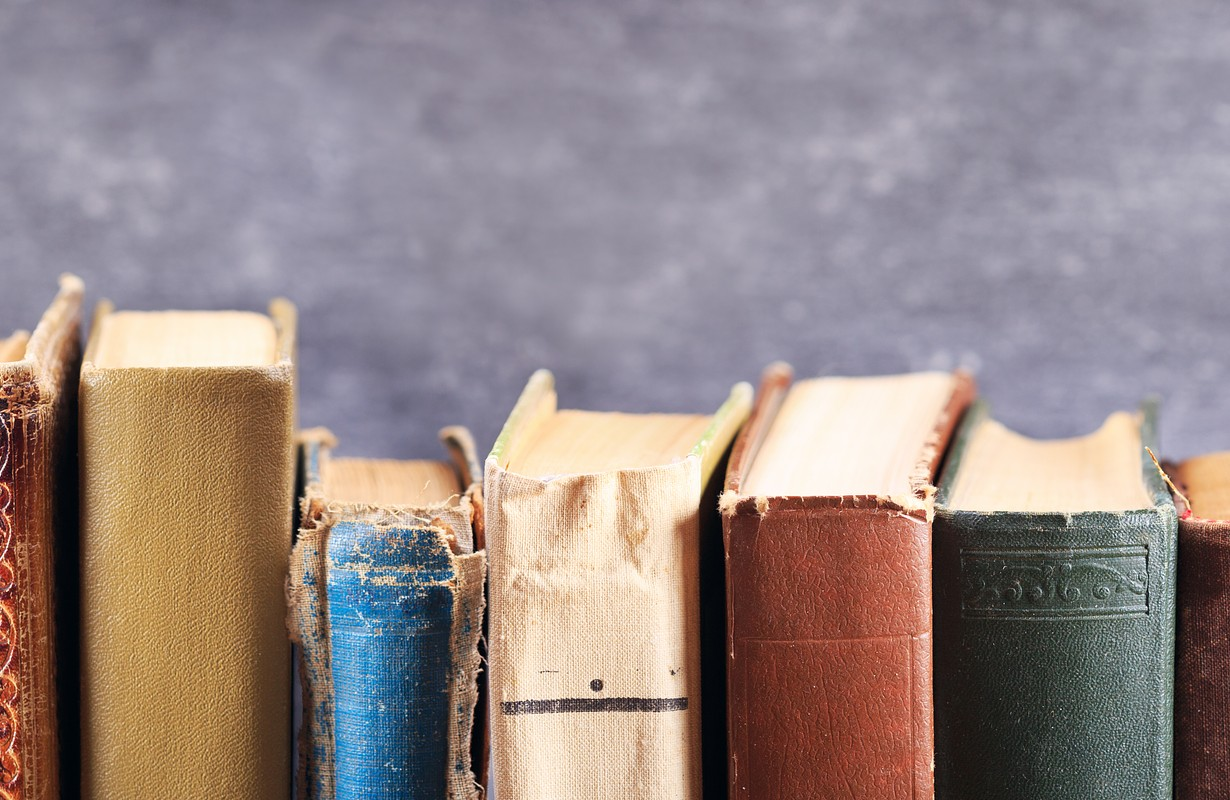 various old books on a shelf on dark background, banner