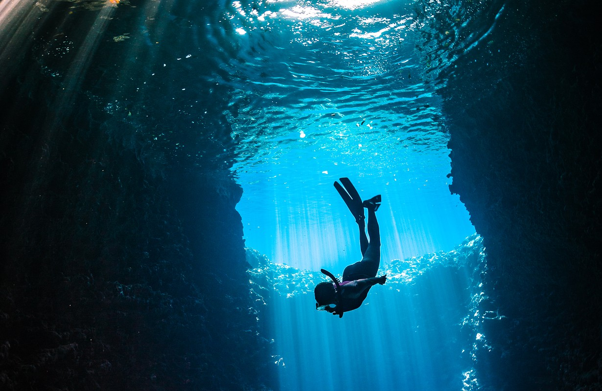 Girl diving in cavern with lightbeams coming on top of her