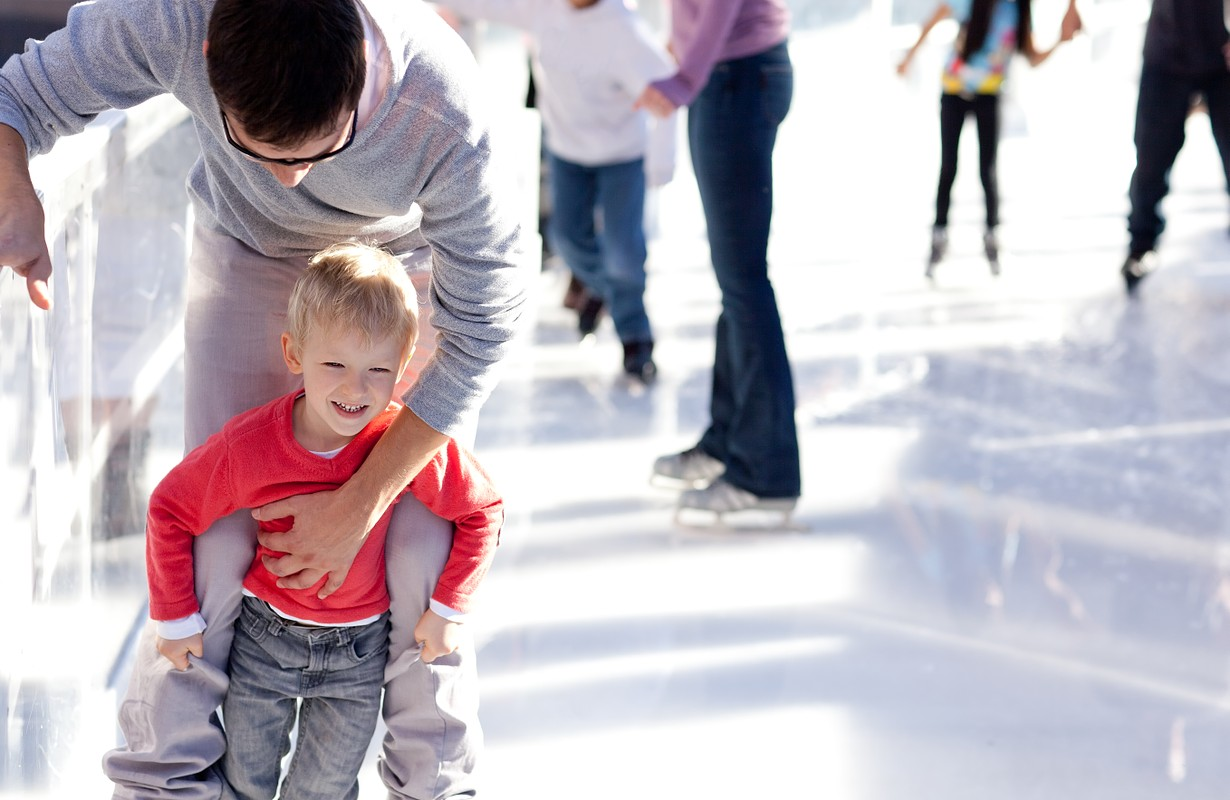 young father teaching his little smiling son ice skating and having fun time