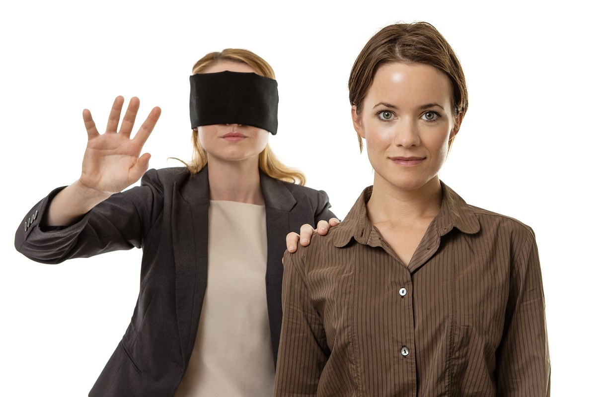 Two women, one blindfolded and the other helping