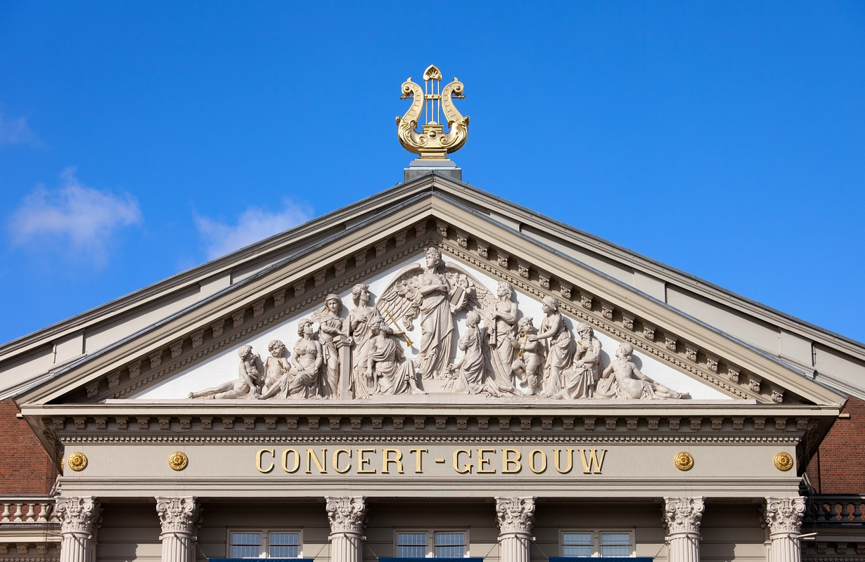 Tympanum with religious reliefs within triangular pediment of the Concertgebouw (concert hall) in Amsterdam, Netherlands, 19th century Neoclassical style.