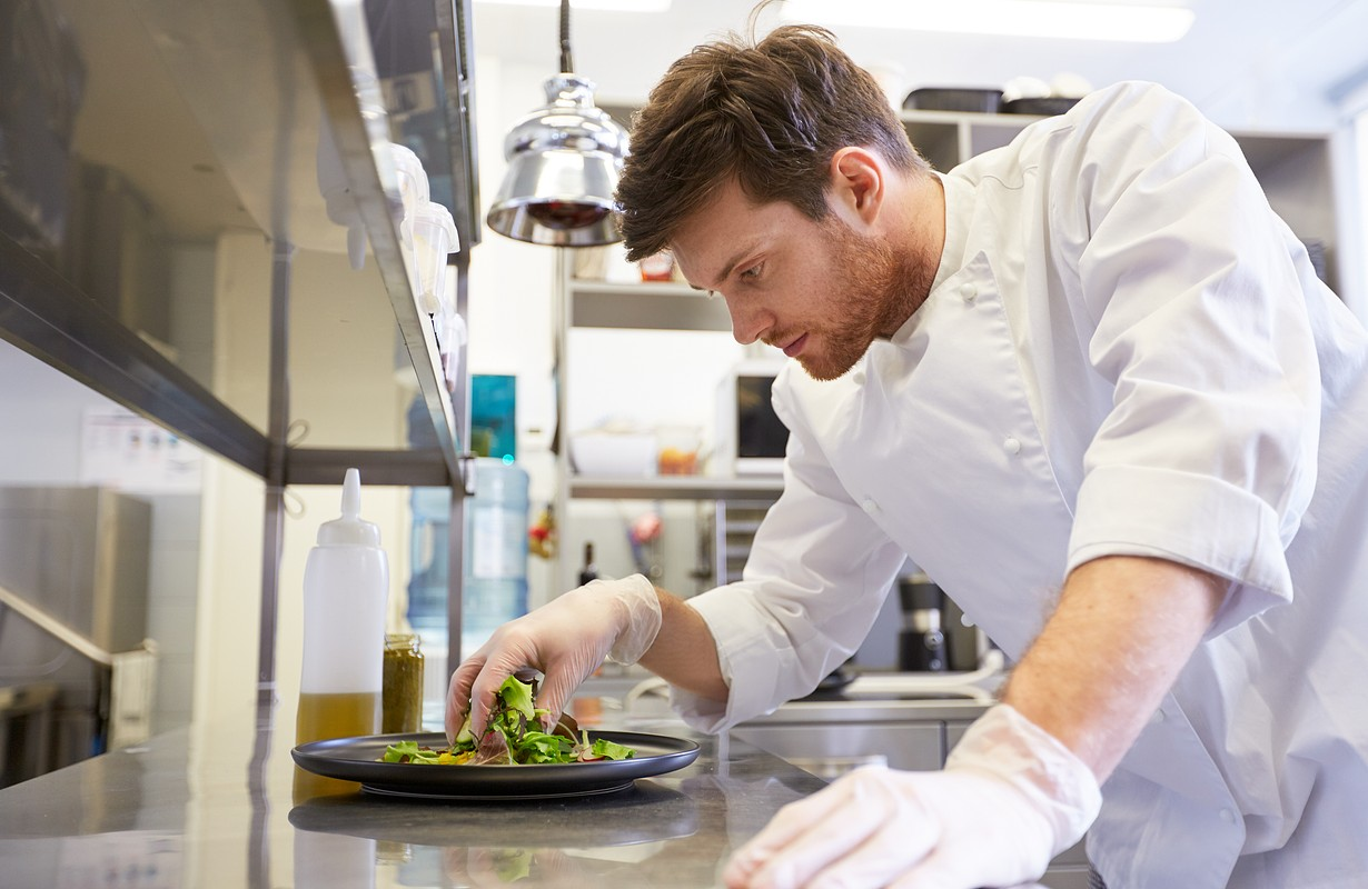 food cooking, profession and people concept - happy male chef cook making vegetable salad at restaurant kitchen
