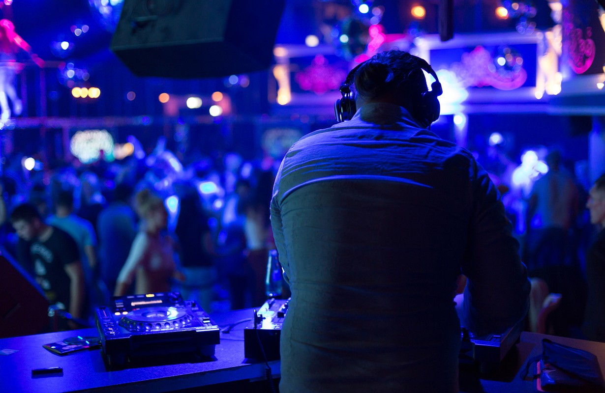 DJ turns the records at the club under the blue light