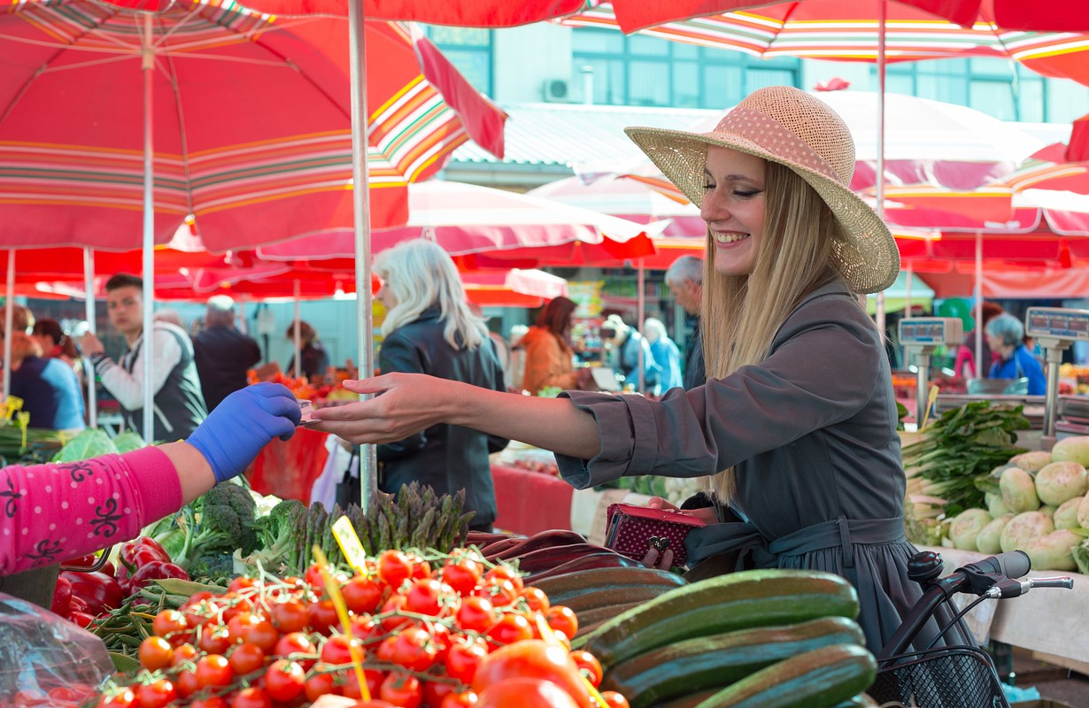 Woman buying vegetables at an outdoor market