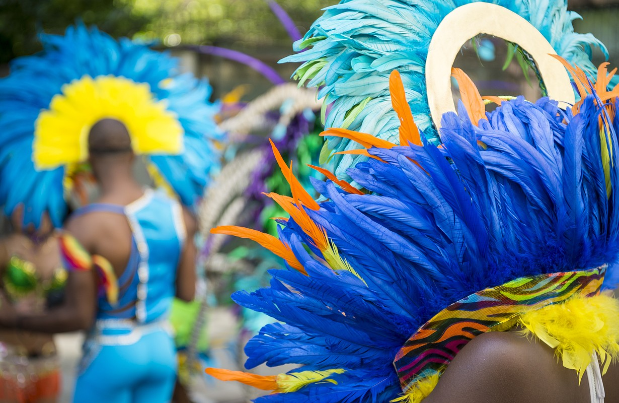 Group of dancers wearing colorful feathers costumes