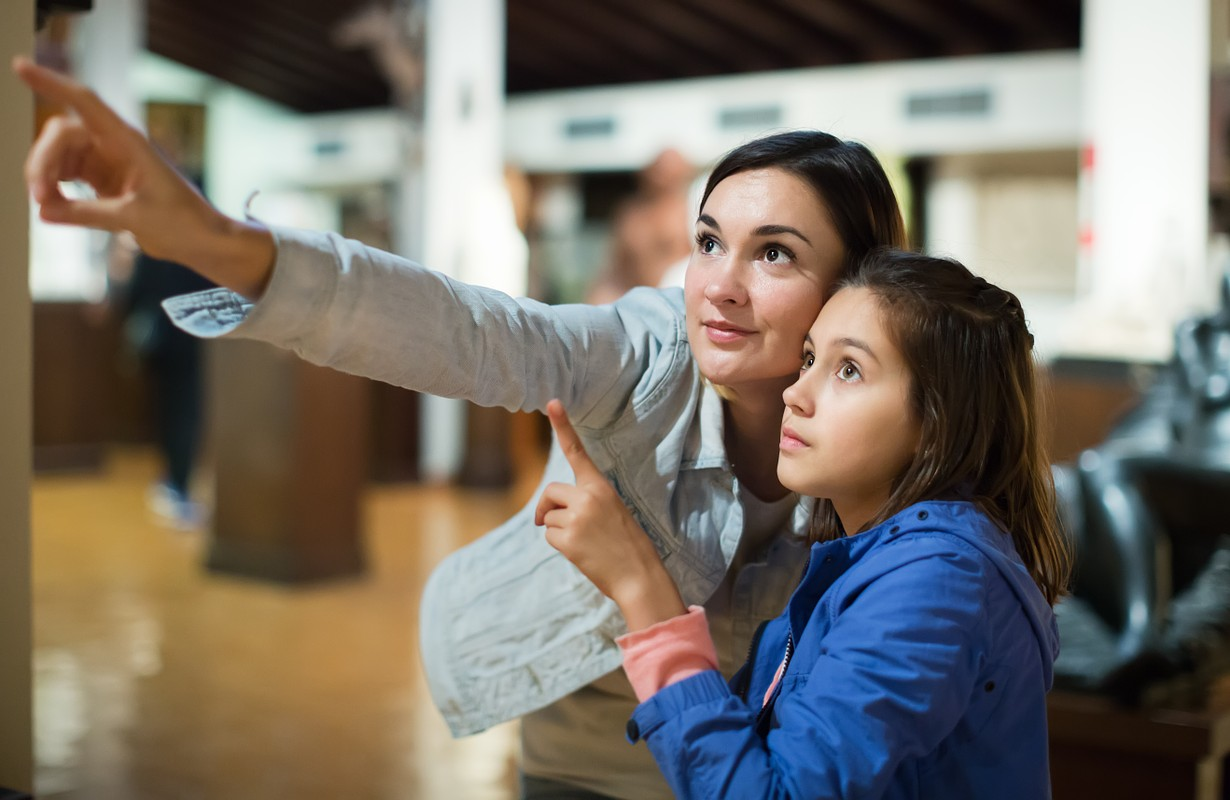 Smiling mother and daughter looking at expositions of previous centuries in museum