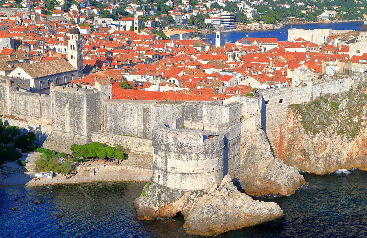 Traditional buildings of Dubrovnik old town surrounded massive walls above the Adriatic sea, Croatia