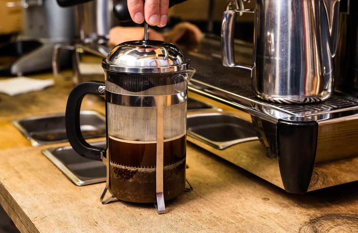 Barista making non traditional coffee in french press, barista coffee preparation service concept