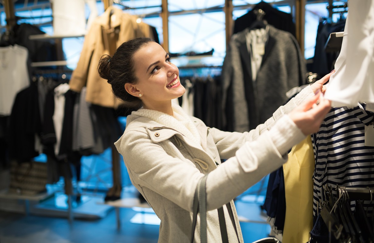 Beautiful shopaholic woman buying clothes