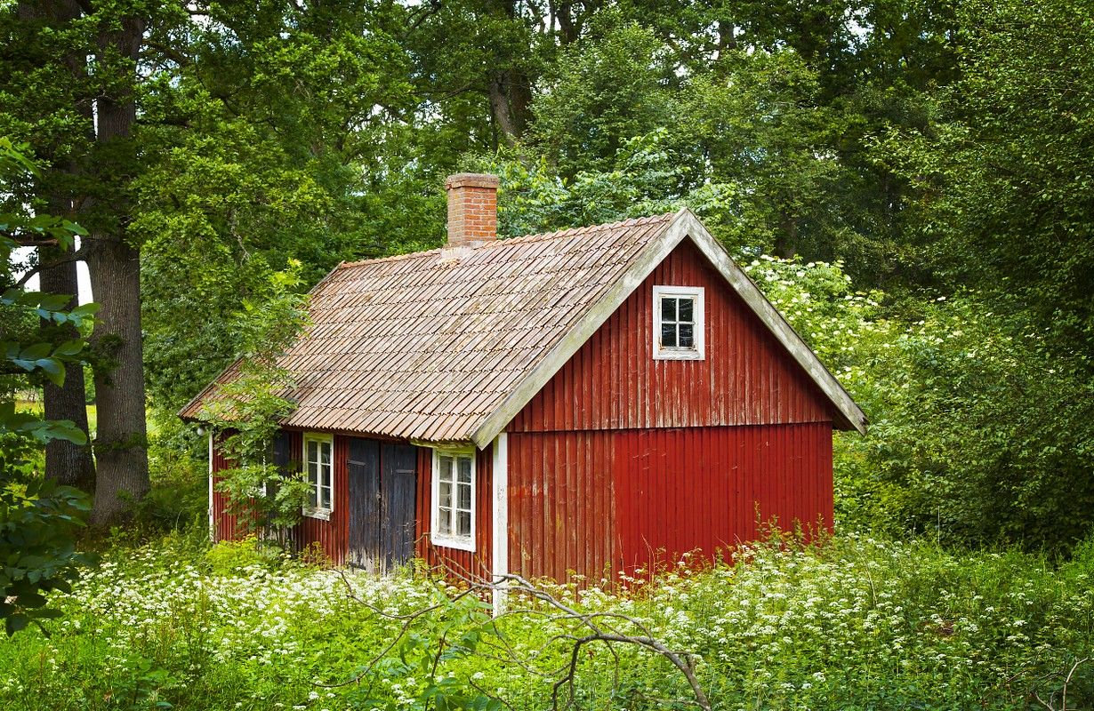 Image of a traditional swedish red wooden cottage, in a rural location