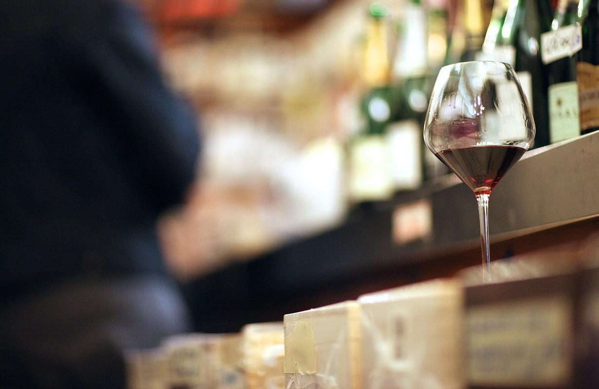 A full wineglass on a shelf in a wine store