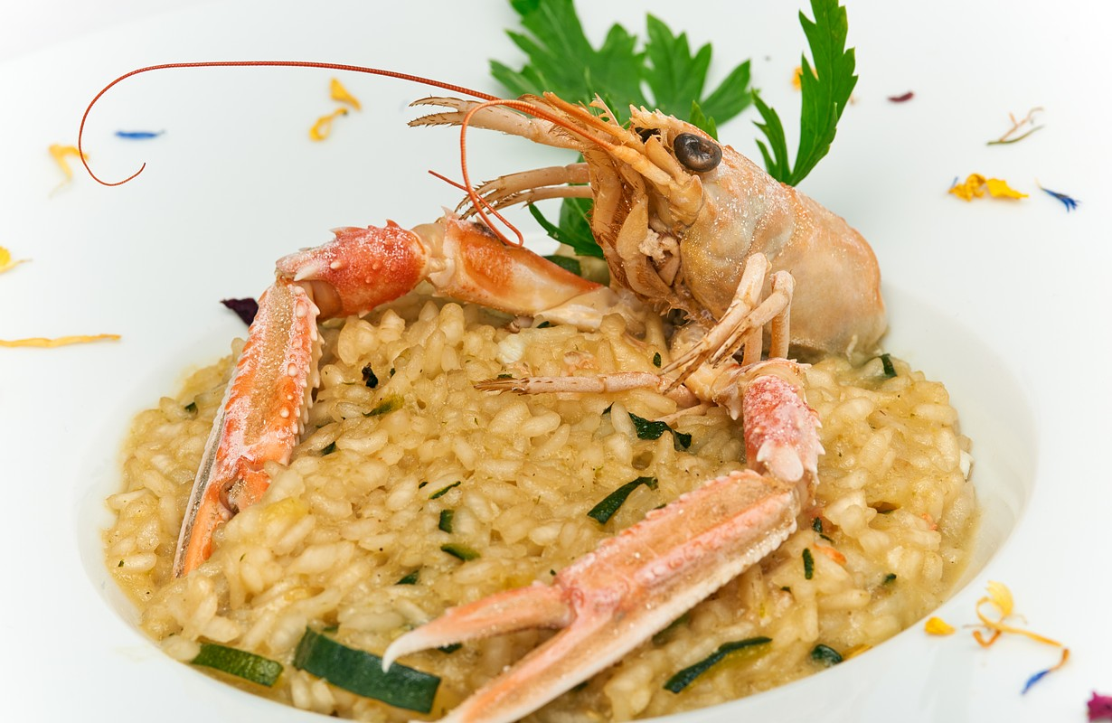 risotto with prawns and zucchini served on white plate