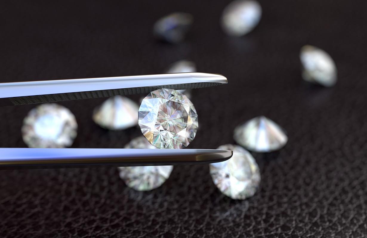 Tweezers holding a white, perfect diamond