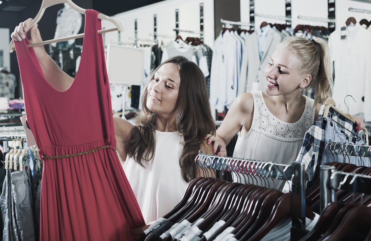 Two positive girls choosing dress together in fashion store