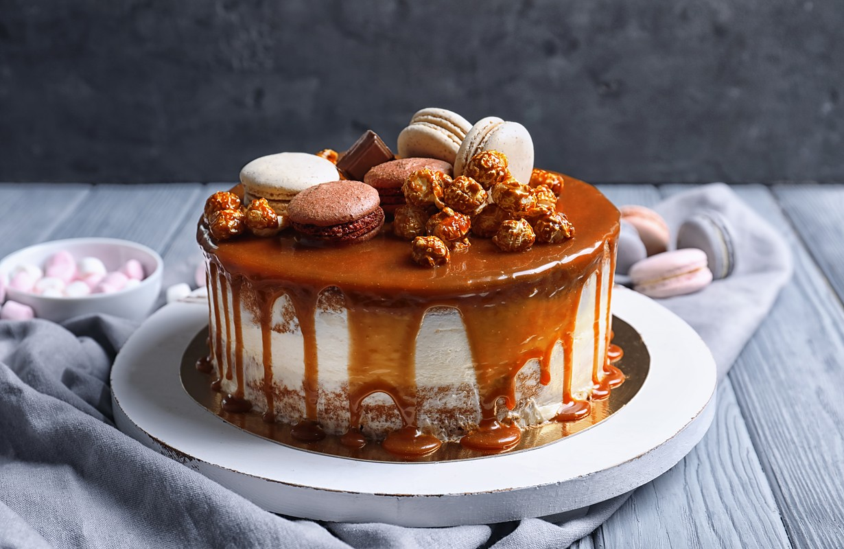 Board with delicious caramel cake on table - Image