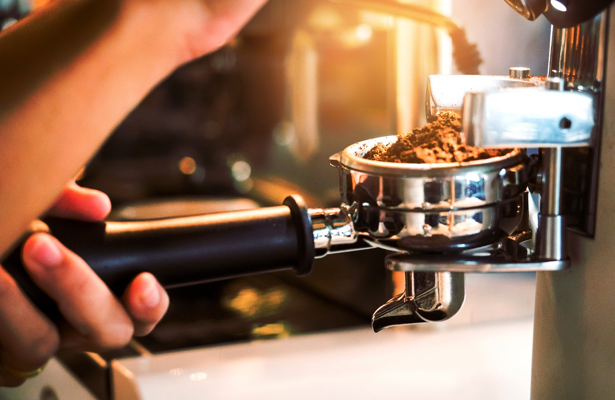 Close-up of espresso pouring from coffee machine. Professional coffee brewing. Focus selection point .