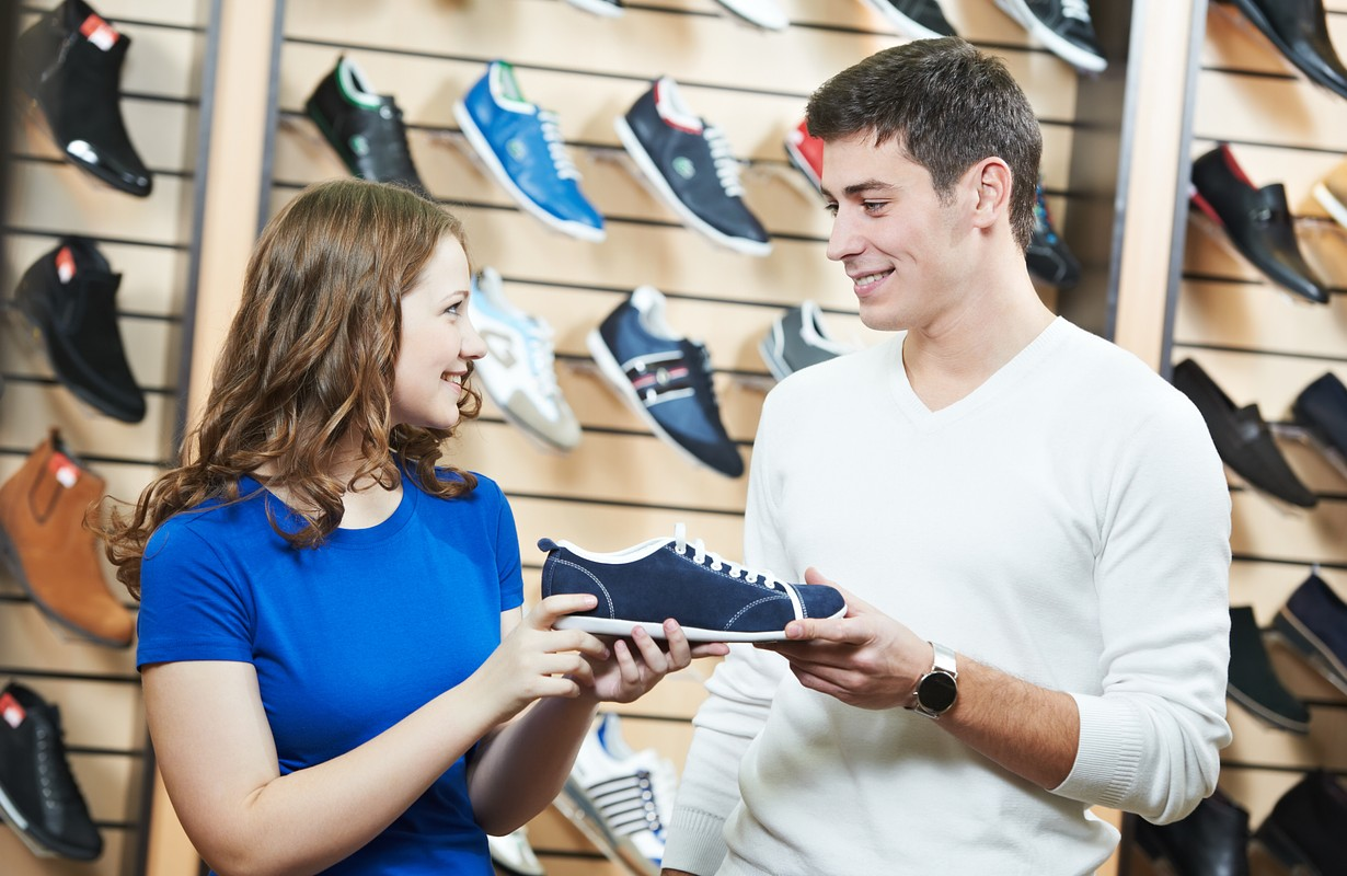 Young man and woman assistant choosing footwear during shopping at shoe shop