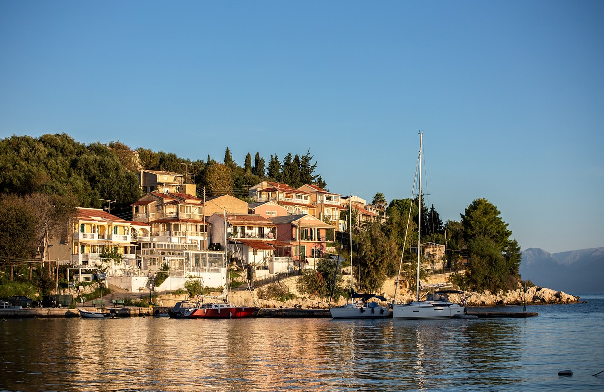 Sunny day in the little village Kassiopi, view from the bay on the hills. Corfu, Ionian islands, Greece