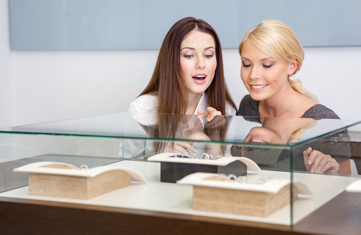 Two women looking at showcase with jewelry at jeweler's shop. Concept of wealth and luxurious life