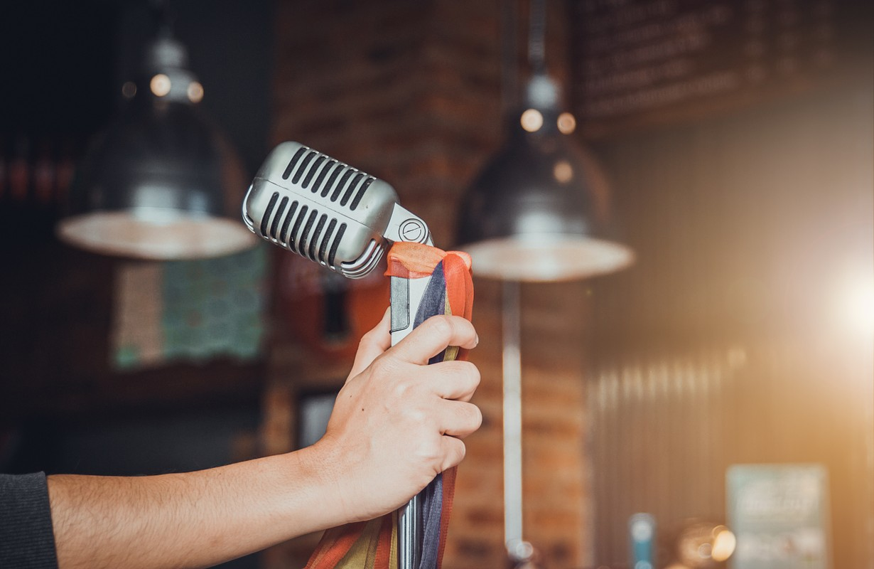 Singer hands holding microphone on stage,Pub,