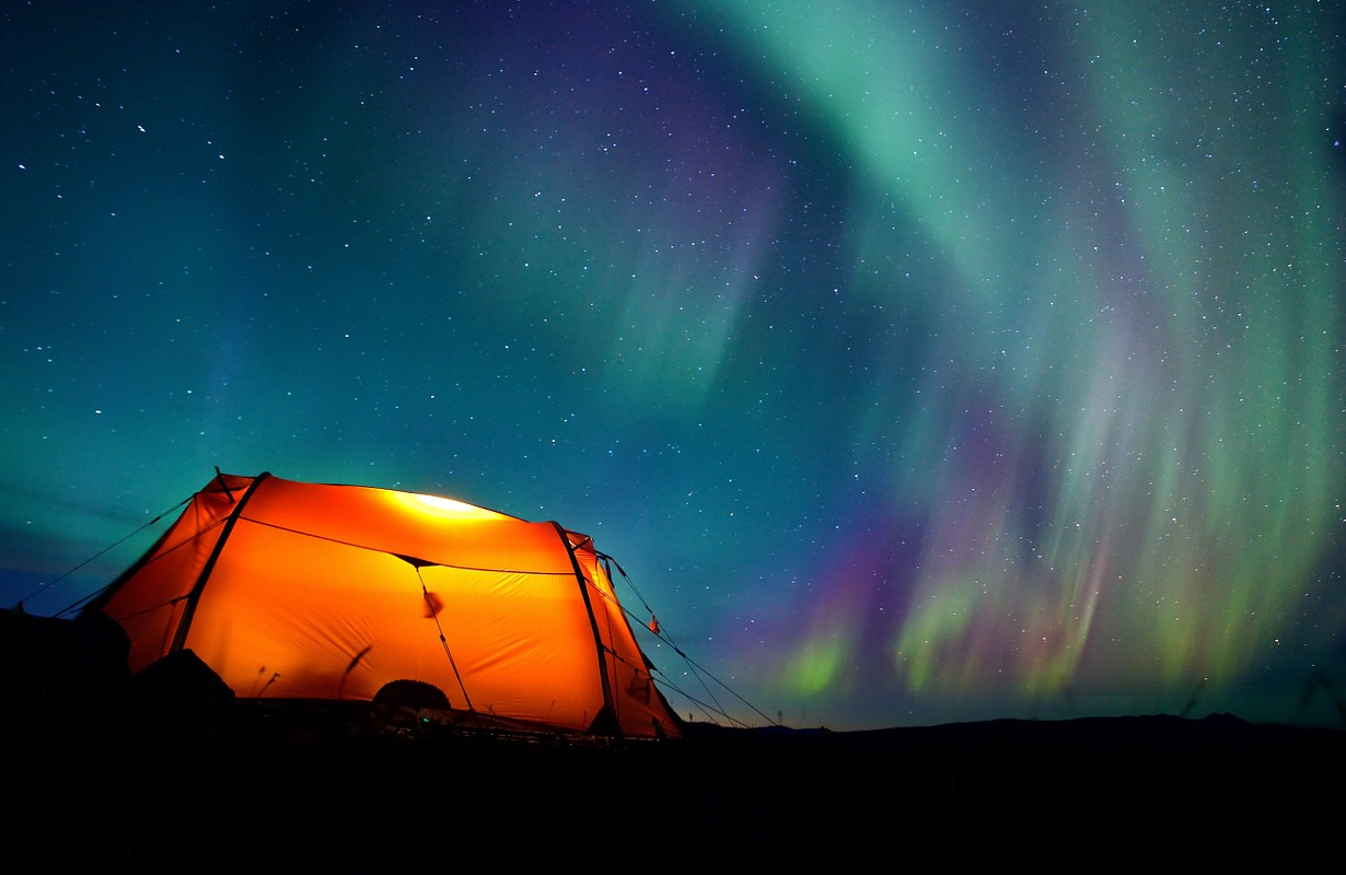 Northern lights over a illuminated tent in Lapland