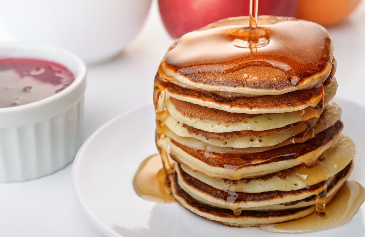 pouring marple syrup on a pancakes stack