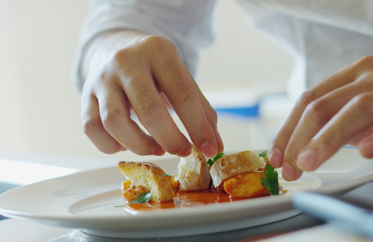 Close up of professional young chef hands garnishing with leaves of parsley a dish which is ready to be served.