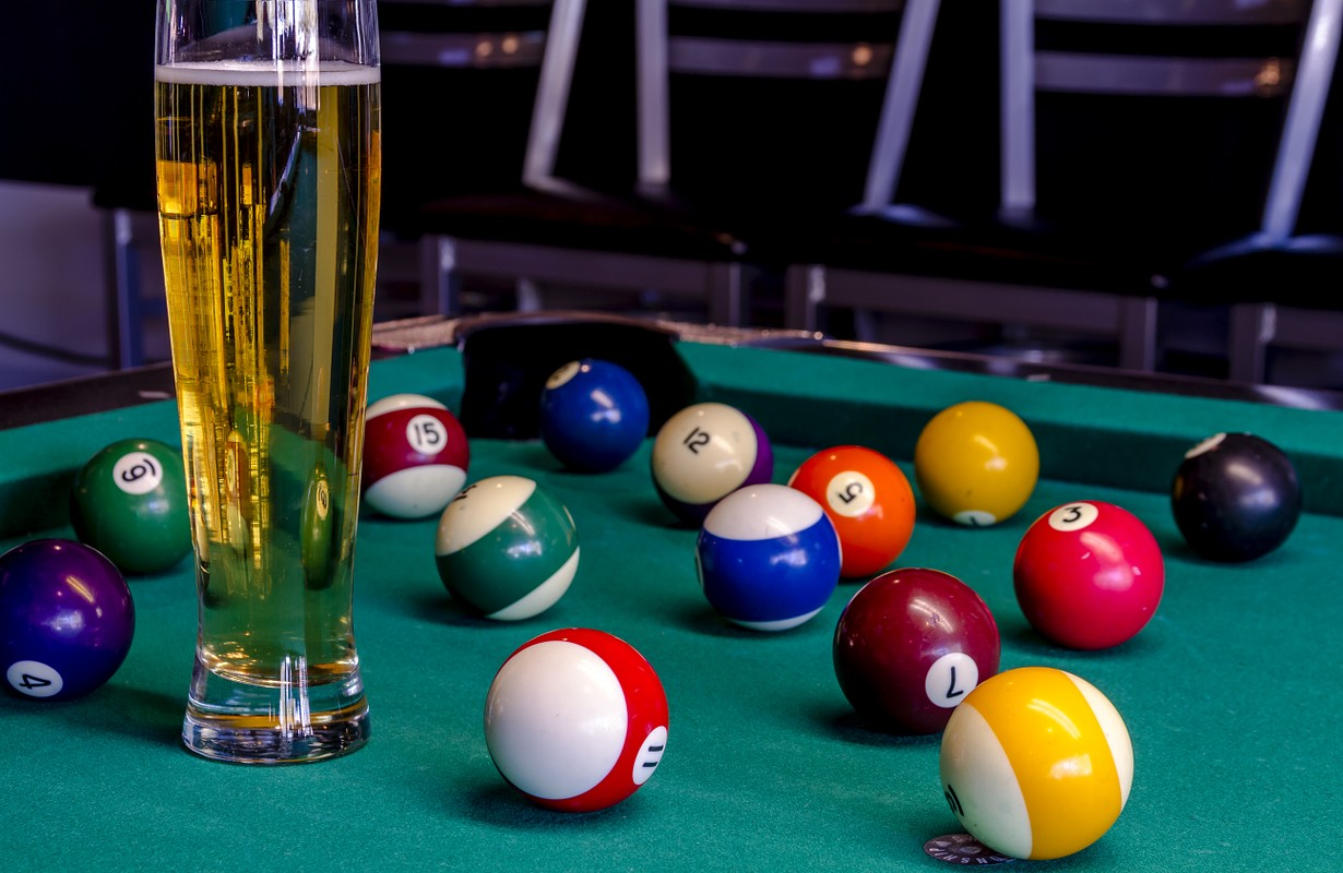 Colorful billiard balls sitting on pool table with glass of beer