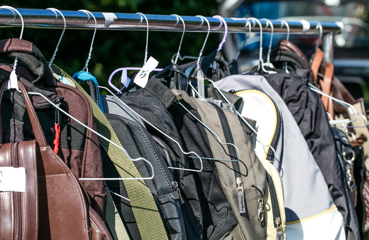 bags and backpack on hanger and rack display at flea market or thrift store to resale, reuse, recycle or exchange outdoor