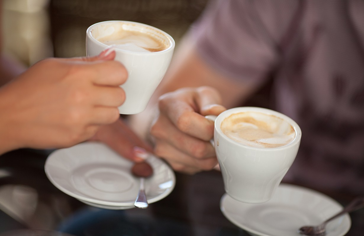 Couple drinking coffee at cafe restaurant man and woman with cup of espresso hot cappuccino on dating. Concept of male and female hands love and coffee. Italian delicious caffeine drink aroma latte