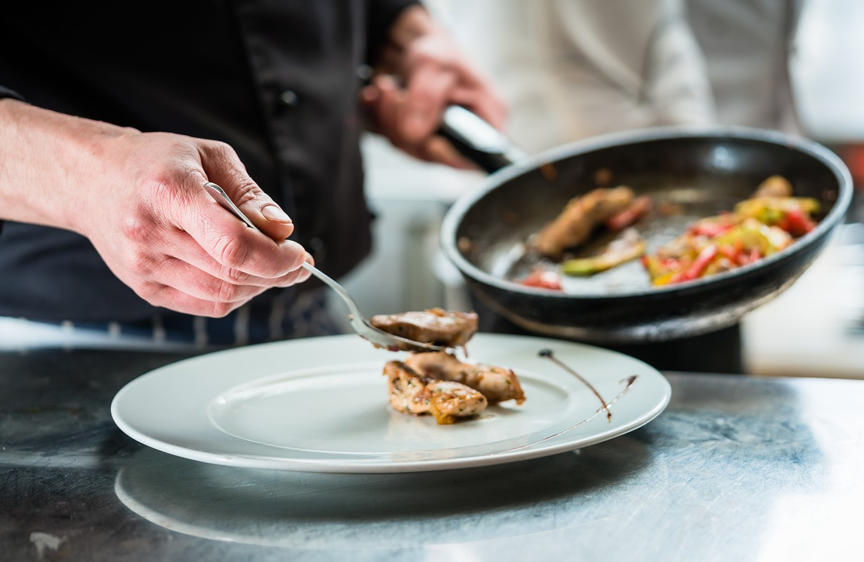 Chef finishing food on plate in restaurant or hotel kitchen