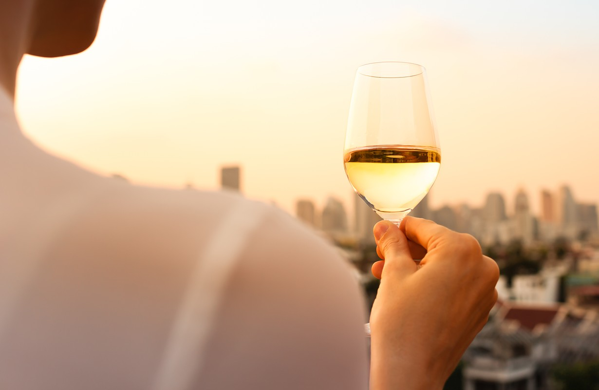 Woman holding a glass of wine while enjoying the city view.