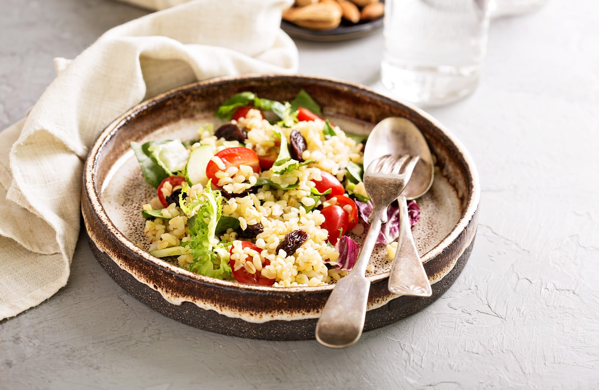 Warm salad with bulgur, vegetables and green leaves