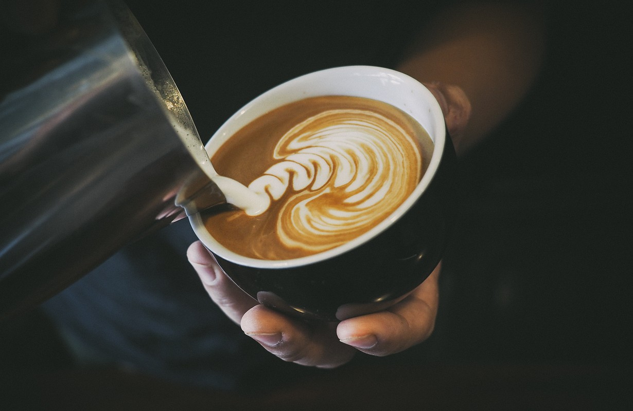 Picture of a barista's hand pouring milk into a cup of coffee - Atlanta, Georgia