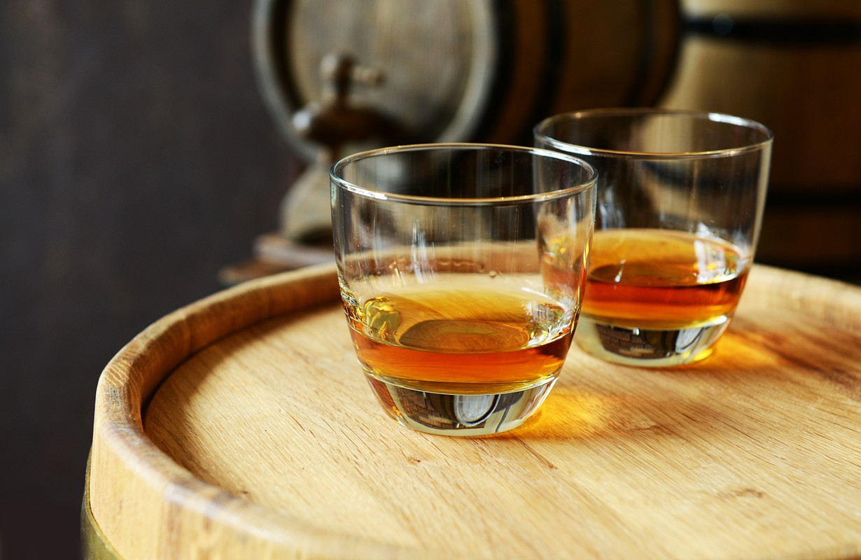 Glasses of alcohol in cellar with old barrels