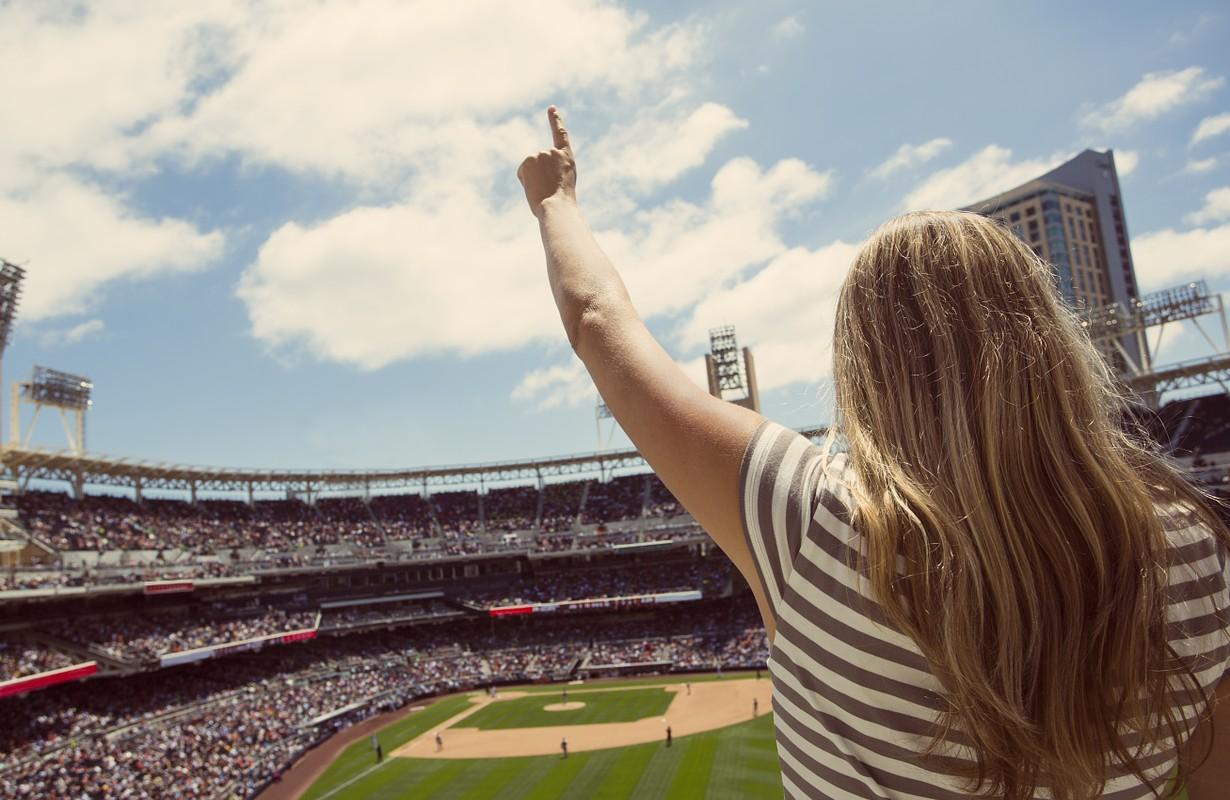Woman standing in a baseball stadium