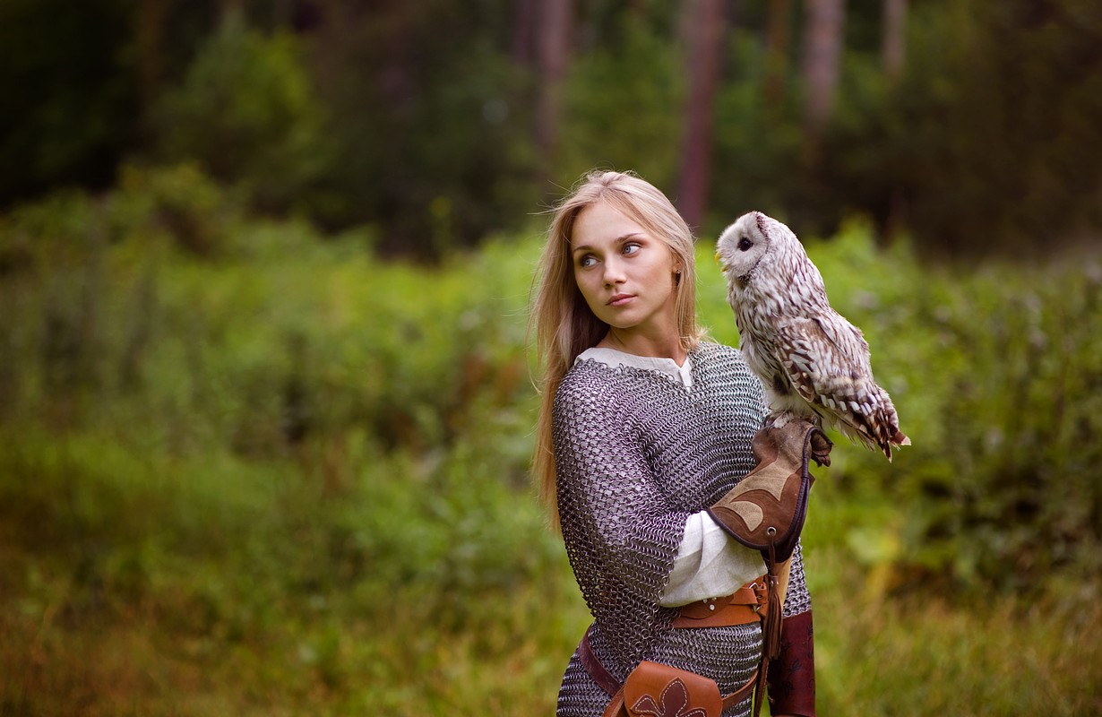 Young woman in chain mail with owl looking away