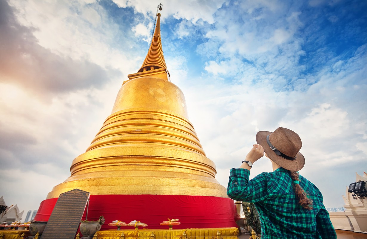Tourist woman in hat and green checked shirt looking at big golden Stupa in Wat Saket temple in Bangkok, Thailand