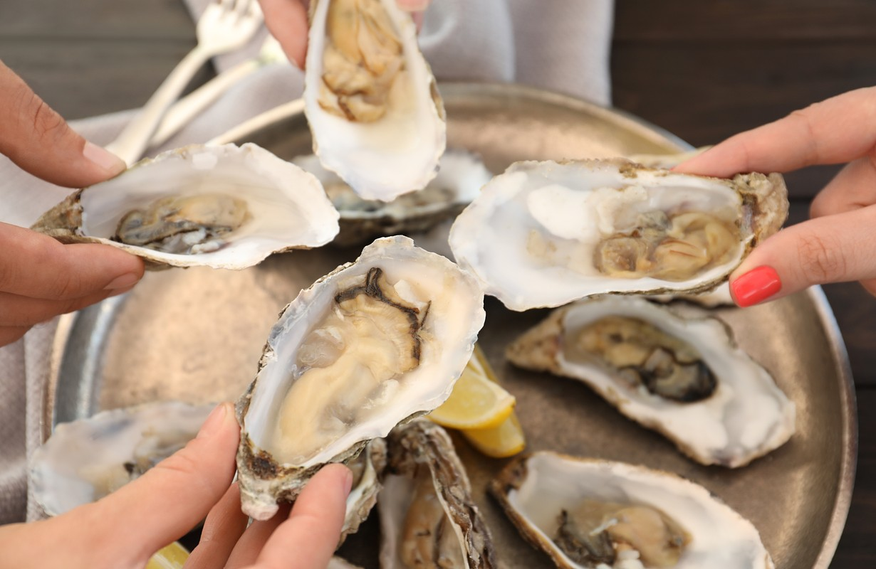 People holding oysters
