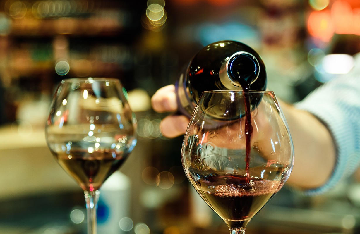 Red wine pouring into a wine glass. Shallow depth of field.