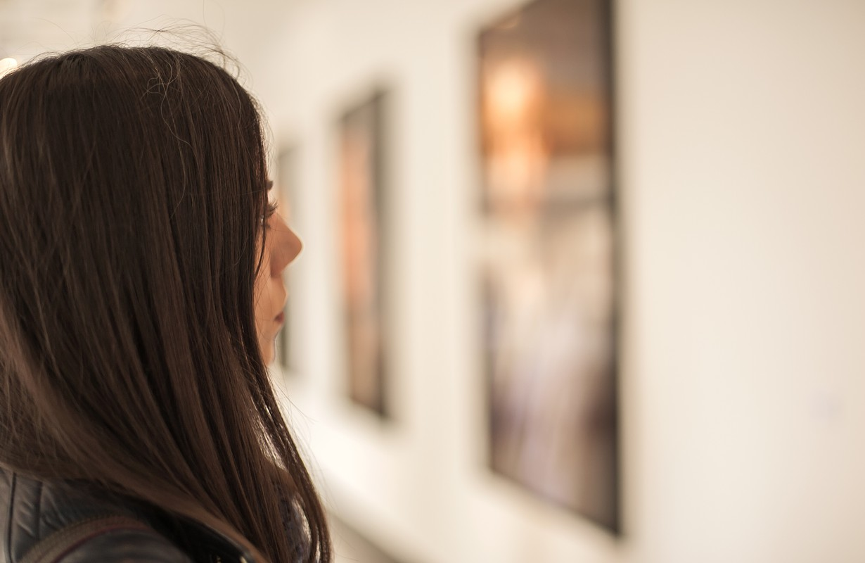 Young woman looking at modern painting in art gallery. Abstract painting