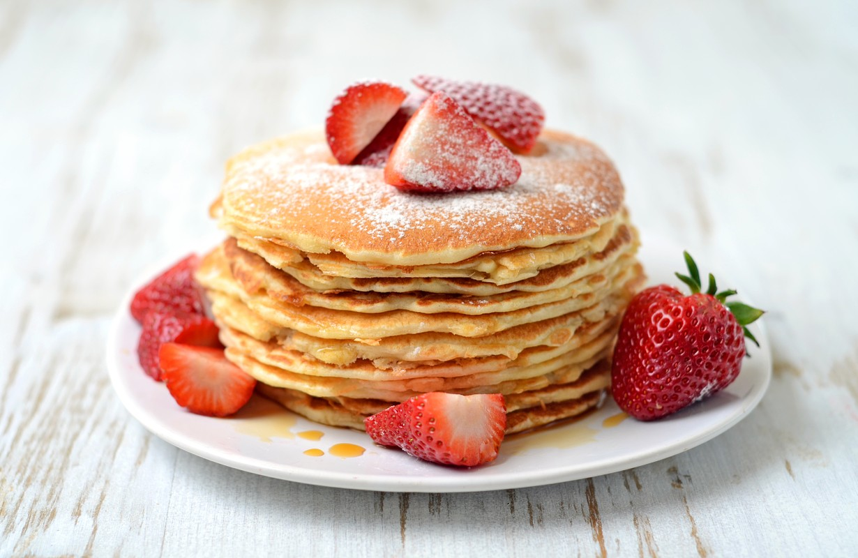 stack of freshly prepared traditional pancakes with strawberries