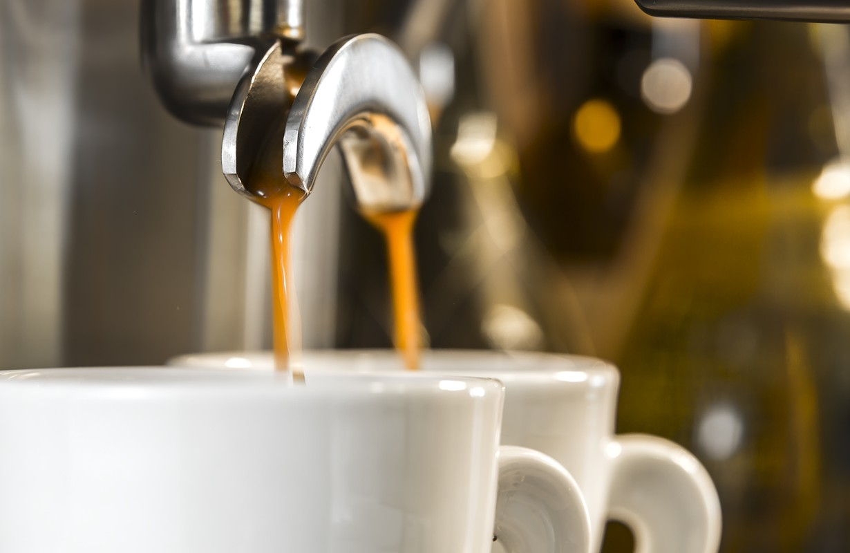 golden espresso flowing into the white porcelain cups