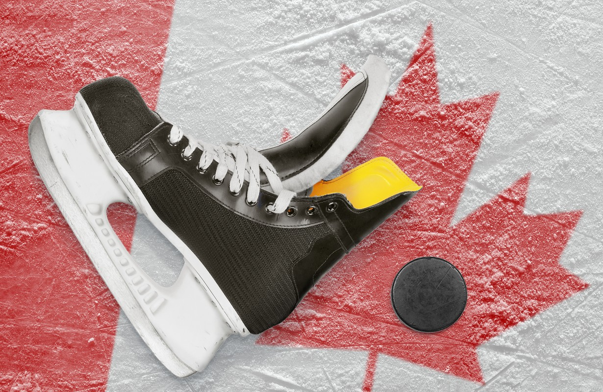 Puck, skates and the image of the Canadian flag on the ice