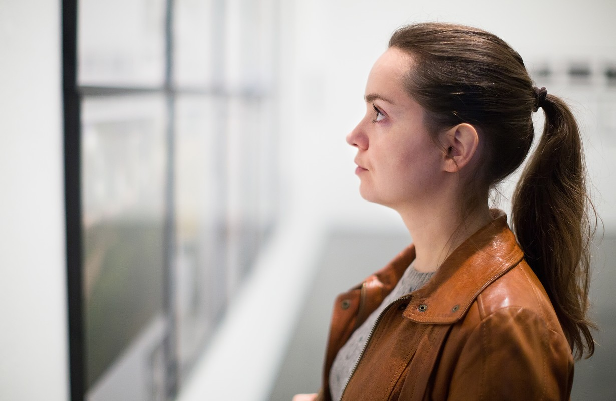 Young brunette woman in leather jacket at gallery exhibition