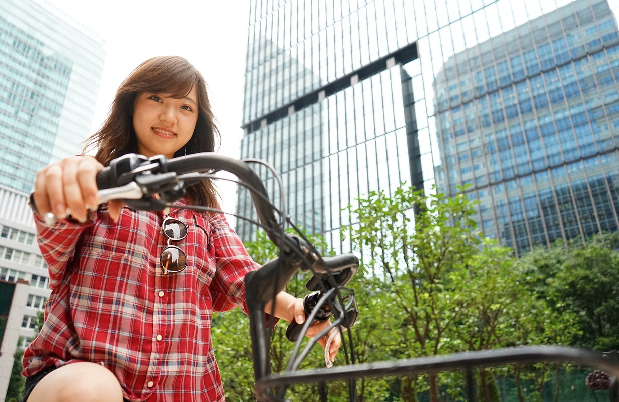 Young Asian woman riding on a bike with smile