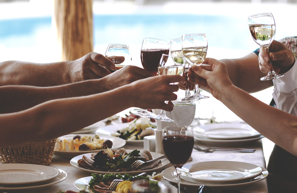 Friends cheering with wine while having different dishes on the table