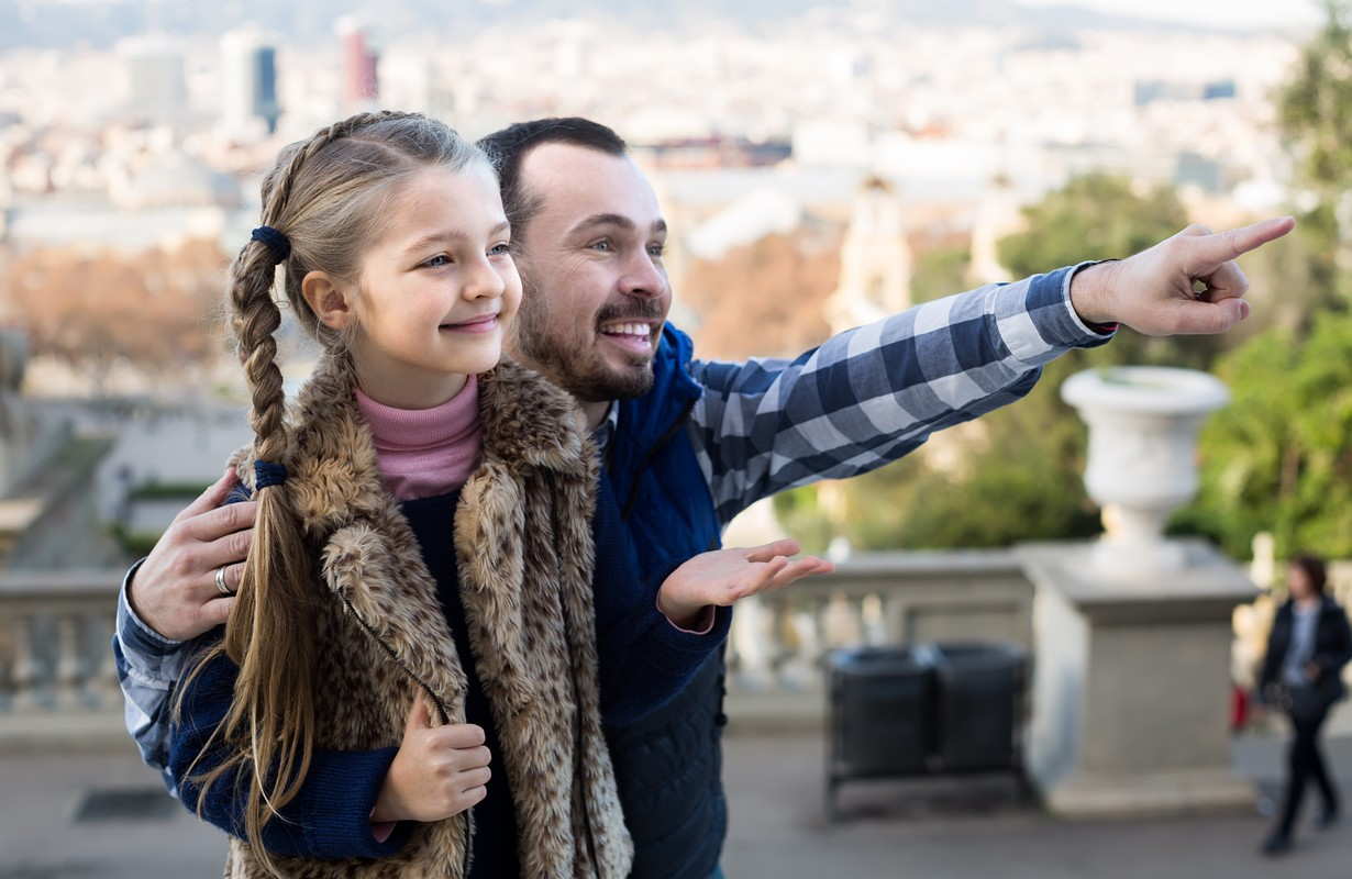 positive father and daughter pointing at sight during sightseeing tour outdoors