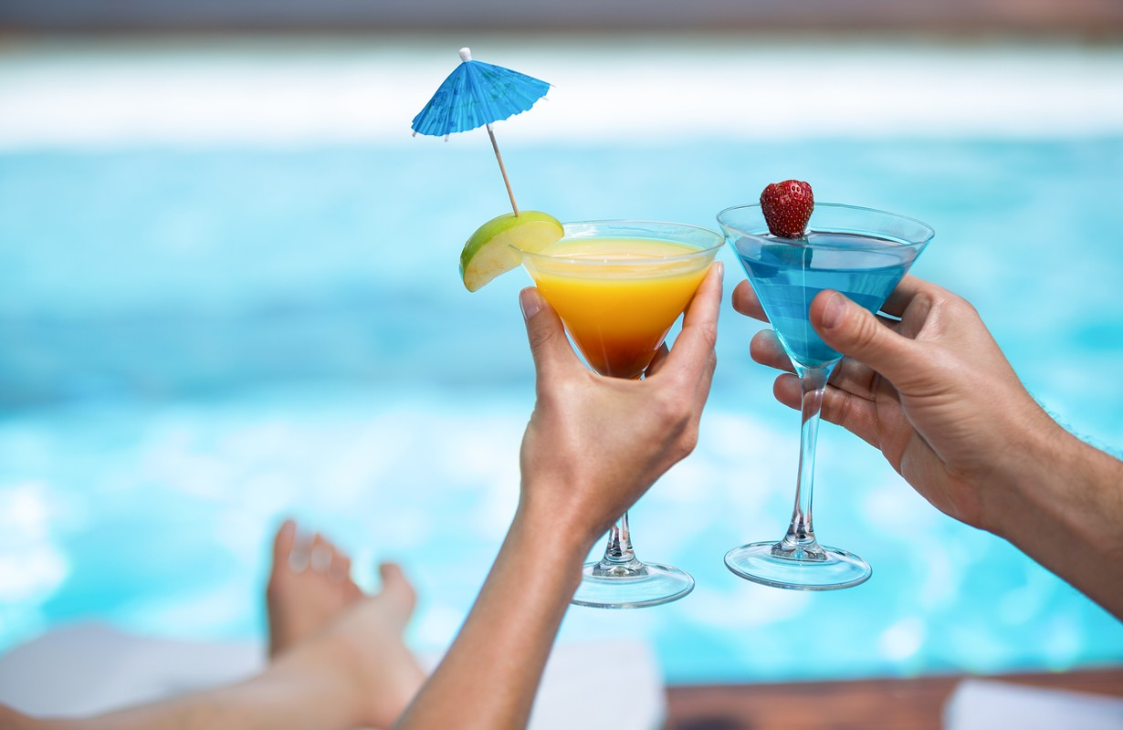 Hands of couple toasting martini glass near pool